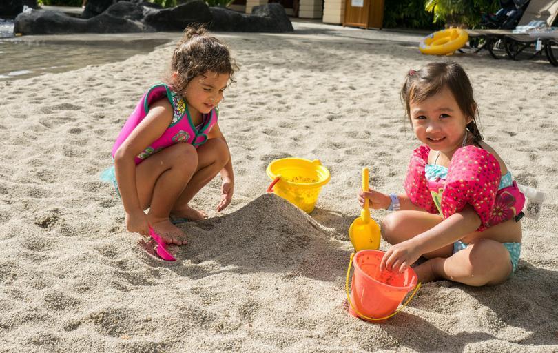 dvě holčičky na pláži, s kyblíkem lopatkou si hrají v písku.jpg